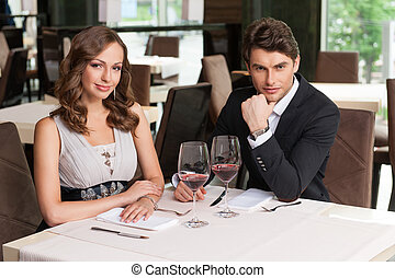 Beautiful couple sitting at the restaurant. Waiting for...