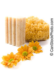 natural sponge, soap and flowers on white background