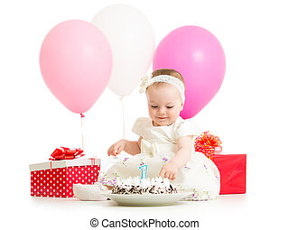 baby girl touching birthday cake