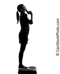 woman standing on weight scale despair aiming gun silhouette...