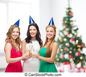 three women wearing hats with champagne glasses -...