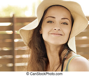 Beautiful smiling woman in hat looking happy outdoors...