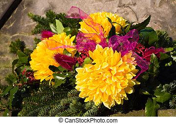 Flowers rest on headstone in cemetery