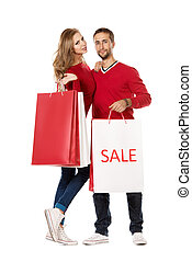 shopping pair - Happy young couple standing with a lot of...