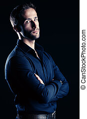 serious male - Modern handsome young man posing over dark...