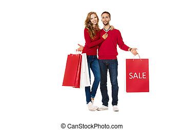 buying presents - Happy young couple standing with a lot of...