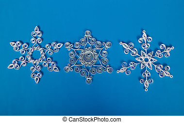 Three paper Christmas snowflakes, self-made. On blue...