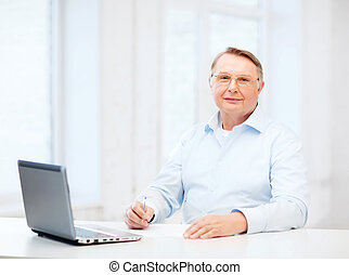 old man in eyeglasses filling a form at home - business,...