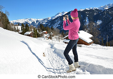 Girl taking a photo in the Swiss Alps