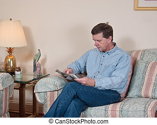 Middle-aged man relaxes on sofa in modern living room...