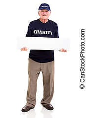 mature charity worker holding blank banner