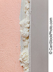 Wall insulation detail - Closeup of gypsum board fixed with...