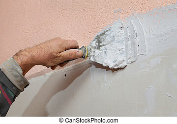 Plaster and gypsum - Worker spreading plaster with trowel to...