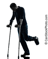 injured man walking with crutches silhouette - one man...