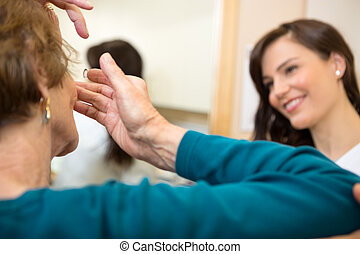 Woman Inserting Contact Lens - Senior woman inserting...