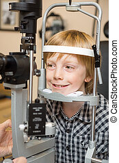 Boy Undergoing Eye Examination Test With Slit Lamp - Smiling...