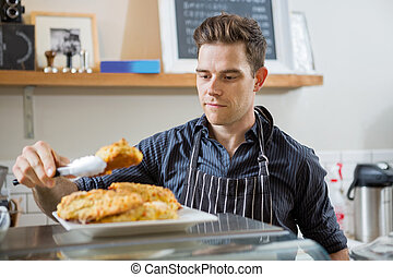 Cafe Owner Serving Sweet Food - Young male cafe owner...