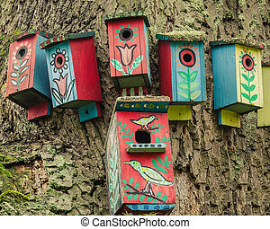 Painted birdhouses on a tree. Symbol of the home