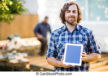 Portrait of carpenter displaying tablet computer with...
