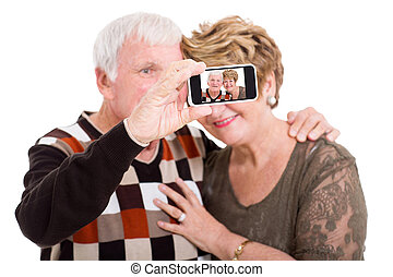 senior couple taking self portrait with smart phone - happy...