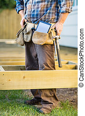 Carpenter With Tablet Computer And Hammer In Tool Belt - Low...