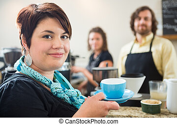 Woman Holding Coffee Cup With Owners in cafe - Portrait of...