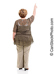 rear view of senior woman pointing at empty copy space on...