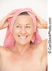 Friendly naked mature woman with towel - Portrait happy...