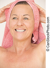 Joyful naked mature woman with towel - Portrait attractive...
