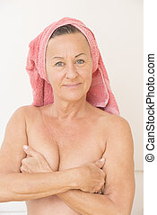 Naked mature woman with hands on breasts - Portrait happy...