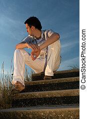 meeting a sunrise - young man sitting on a flight of stairs...