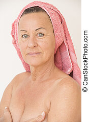 Nude mature woman with hands on breasts - Portrait happy...