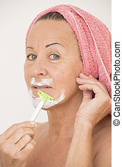 Mature woman shaving face with lotion - Portrait attractive...