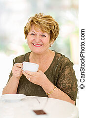 mature woman drinking coffee - happy mature woman drinking...