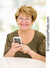 senior woman using smart phone - cheerful senior woman using...