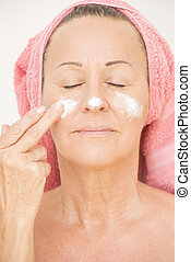 Woman putting cream on face - Portrait attractive relaxed...
