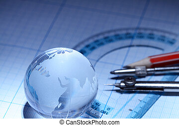 World education - Glassy globe and drawing tools lying on...