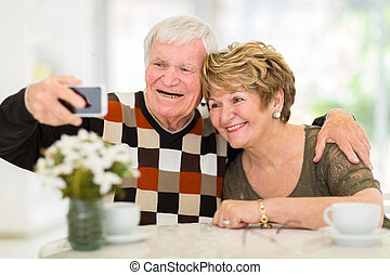 senior couple using cell phone at home - cheerful senior...