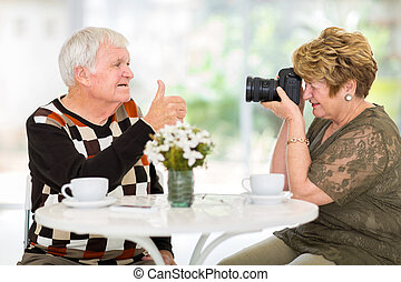 senior wife taking a photo of her husband with digital SLR...