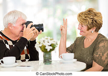 elderly man photographing his wife with a digital camera