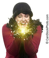 Excited Woman Wearing Winter Hat, Scarf and Gloves Holds Something Magical and Sparkling in the Palms of Her Hands Against White Background.