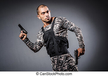 Soldier with guns against dark background