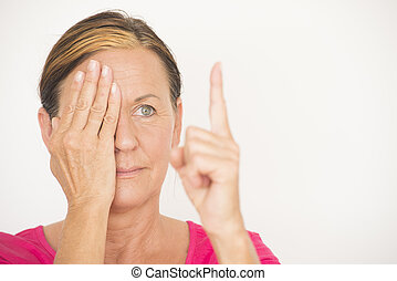 Mature woman testing focus of eyesight - Portrait attractive...