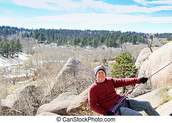 Rock Rappelling senior male #1 - Happy Senior male climbing...