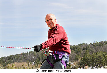 Rock rappelling senior male #2 - Happy Senior male climbing...