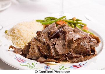 Gyro doner garnished with rice pilaf and vegetables served...