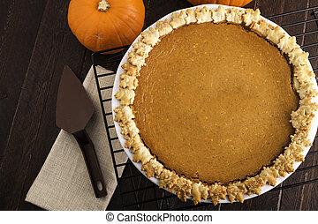 Pumpkin Pie - Whole pumpkin pie on wire rack sitting on...