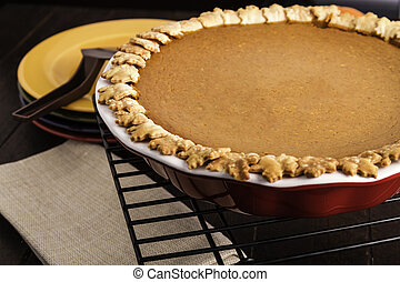 Pumpkin Pie - Pumpkin pie sitting on wire baking rack with...