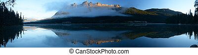 Panoramic image Lucerne Peak lit by the rising sun reflected...