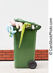 Toys in litter bin - Plush toys stuffed in a green litter...